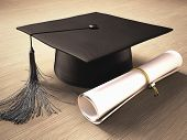 stock photo of degree  - Graduation cap with diploma over the table - JPG
