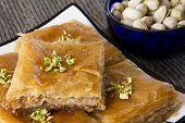 stock photo of baklava  - Baklava on a Plate with a Bowl of Pistachios - JPG