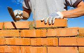 image of bricklayer  - bricklayer laying bricks to make a wall - JPG