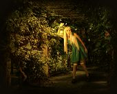 pic of kerosene lamp  - Young blond woman in dress walking on a mysterious path into an enchanted forest - JPG