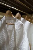 picture of housecoat  - Close up white robes with wooden hangers - JPG