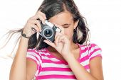 Beautiful young girl taking a picture with a vintage looking compact camera looking through the view
