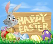 stock photo of ester  - Easter wood sign in spring field reading Happy Easter with the Easter bunny and decorated Easter eggs - JPG