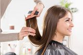 stock photo of hair cutting  - Young beautiful woman having her hair cut at the hairdresser - JPG