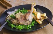 stock photo of roast duck  - Roast duck leg with steamed curly kale and roast parsnips - JPG