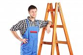 stock photo of jumpsuits  - Male worker in jumpsuit standing next to a ladder isolated on white background - JPG