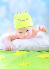 pic of baby frog  - Closeup portrait of cute little baby wearing funny frog costume and lying down on imagine floral field at home - JPG