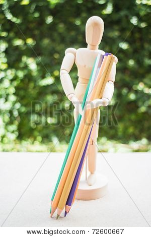 Wooden Manikin Carrying Colour Pencil On Artist Work Table