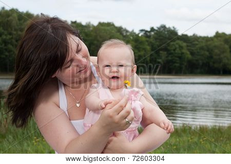 Smiling Mother With Her Baby And The Flower