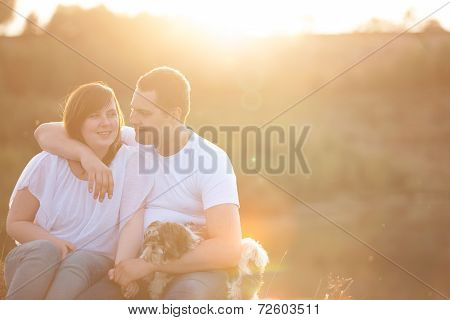Young Couple And Puppy In Sunlight