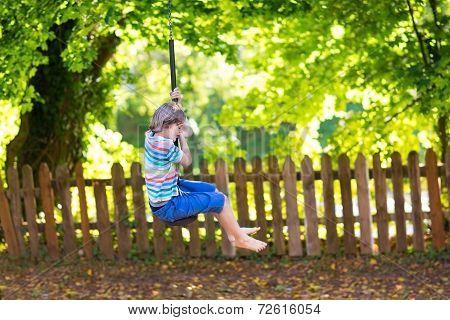 Cute School Boy Enjoying A Swing Ride On A Playground On A Warm Sunny Summer Day