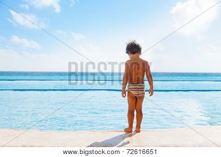Boy stands on stone boarder of swimming pool