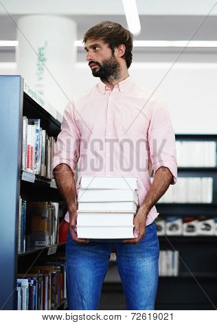 Young male student standing near bookshelf in library, student of high school