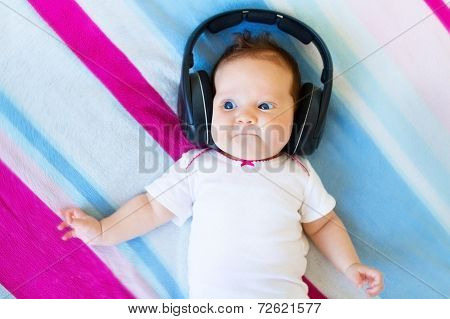 Funny Newborn Baby Relaxing On A Colorful Blanket Listening To The Music With Huge Earphones