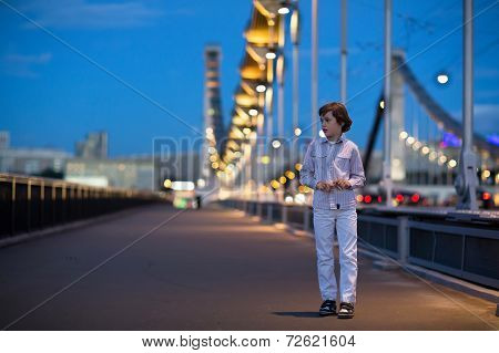 Little Boy Walking Alone Scared On A Beautiful Bridge In A Dark City By Night