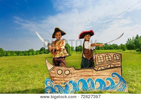 African boy, girl in pirates costumes with swords