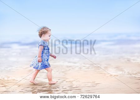 Cute Toddler Girl In A Blue Dress Walking On A Beach At Sunset