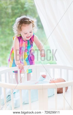 Cute Laughing Toddler Girl Playing With Her Newborn Baby Brother In A White Bedroom With Big Window