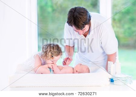 Cute Toddler Girl Kissing Her Newborn Baby Brother On A White Changing Table Next To A Big Window