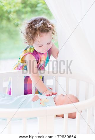 Cute Toddler Girl Playing With Her Newborn Baby Brother Laying In A White Round Crib