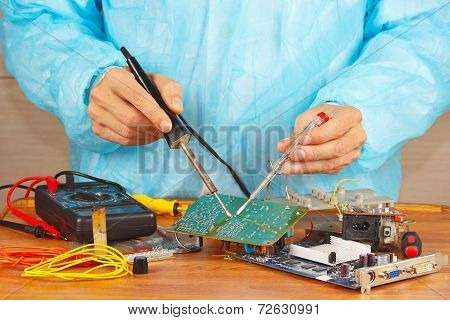 Serviceman solder electronic board of device in service workshop