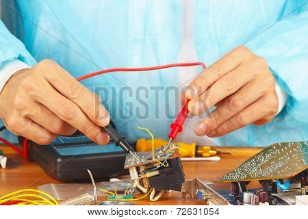Serviceman measures the parameters of the electronic device with multimeter