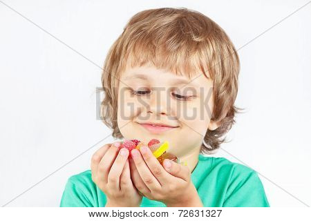 Smiling child with sweets and jelly candies on white background