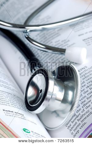 A stethoscope on the top of a medical reference book