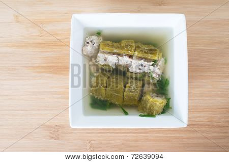 Vietnamese Stuffed Bitter Melon Soup, Canh Kho Qua Nhoi Thit  Against Wooden Board Background
