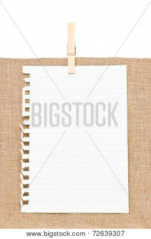 Ripped Off Paper With Wooden Clothespin On Burlap.