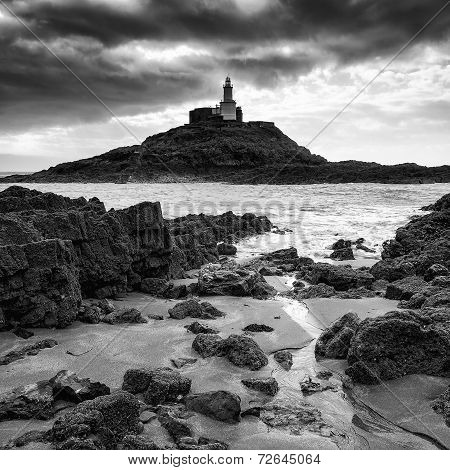 Lighthouse Landscape With Stormy Sky Over Sea With Rocks In Foreground In Black And White