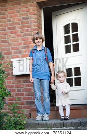 Brother And Baby Sister Leaving Home On Their First Day To School And Kindergarten