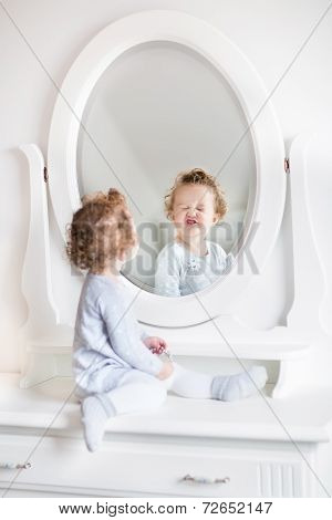Very Funny Baby Girl With Curly Hair Looking At Her Reflection In Mirror In Beautiful White Bedroom