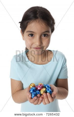 Little girl with a handful of chocolate eastern eggs