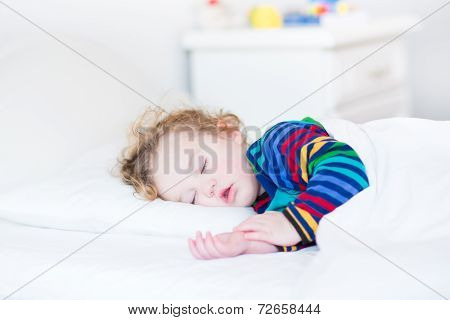 Adorable Toddler Girl Taking A Nap In A White Sunny Bedroom