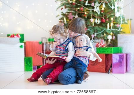 Portrait Of Thre Kids Reading A Book Under A Christmas Tree
