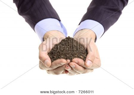 Hands holding a pile of soil