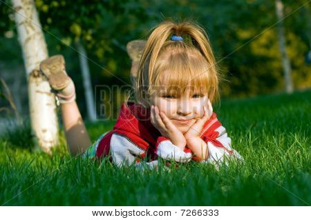 The Small Beautiful Girl Sits On A Green Lawn