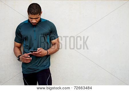 Handsome sportsman holding mobile phone and looking for the mobile screen standing outdoors