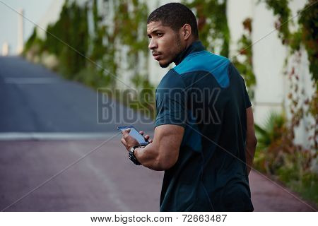 Handsome dark skinned jogger relaxing after workout outdoors, muscular body man using mobile phone