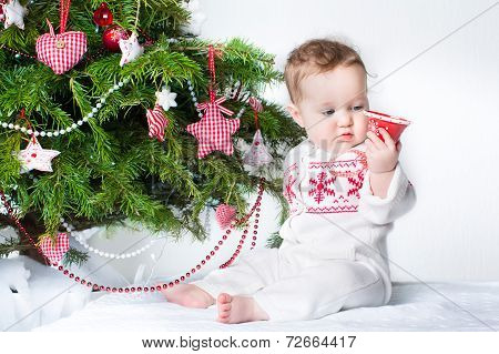 Adorable baby girl playing with a toy bell under a Christmas tree