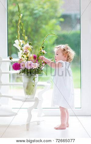 Portrait of a beautiful baby girl playing with fresh flowers wearing a white dress