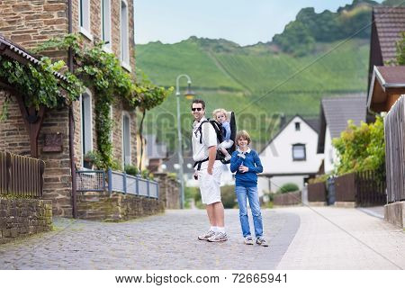 Young Father Hiking With His Son And Baby Daughter In A Traditional Small German Village