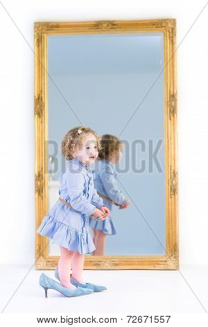 Cute Toddler Girl With Curly Hair Wearing A Blue Dress Is Putting On Her Mother's High Heels Shoes