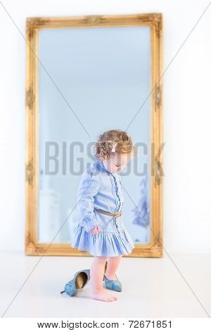 Adorable Toddler Girl With Curly Hair Wearing Blue Dress Is Trying To Put On Her Mother's Shoes