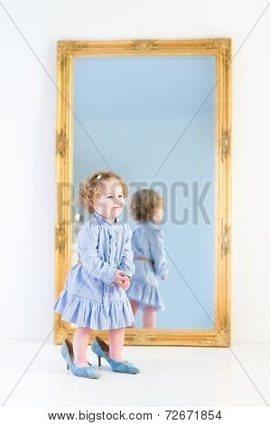 Beautiful Toddler Girl With Curly Hair In Blue Dress In Front Of A Big Mirror Trying mother's Shoes