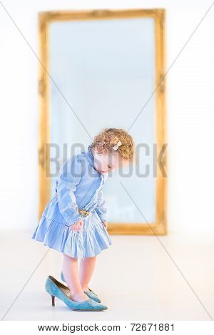 Funny Toddler Girl With Curly Hair Wearing A Blue Dress Is Trying On Her Mother's Shoes