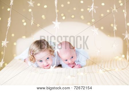 Cute Toddler Girl And Her Little Newborn Baby Brother In Bed With lights around them