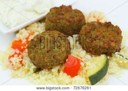 Falafel with couscous and vegetables, close up