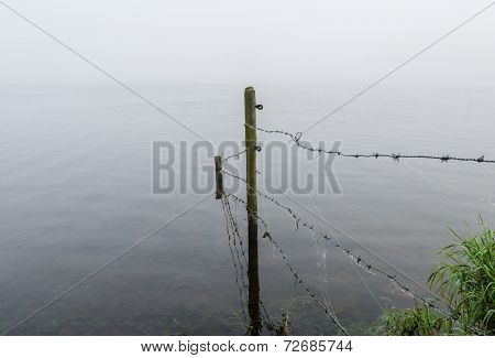 Wooden Poles And Barbed Wire Reflected In The Mirror Smooth Water Surface